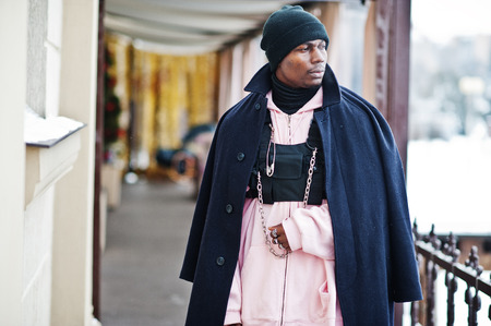 Stylish urban style african american man in black coat and hat, pink hoodie posed at winter day. Stock Photo