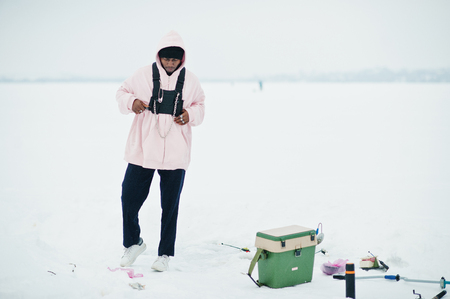 African american fisherman on frozen sea. Winter fishing.