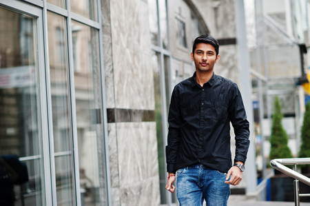 Stylish indian model man in casual clothes, black shirt posed outdoor at street of India.