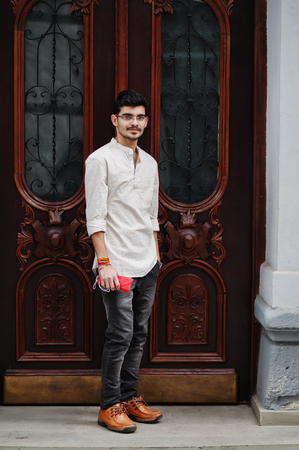 Stylish indian model man in casual clothes and eyeglasses posed outdoor at street of India.