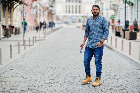 Stylish indian beard model man in casual clothes posed outdoor at street of India.