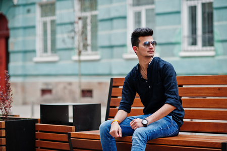 Stylish indian model man in casual clothes, black shirt and sunglasses posed outdoor at street of India and sitting on bench. Imagens