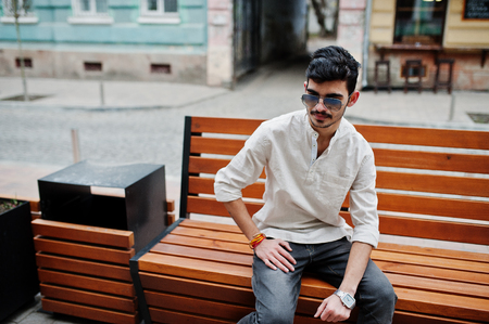 Stylish indian model man in casual clothes and sunglasses posed outdoor at street of India and sitting on bench.