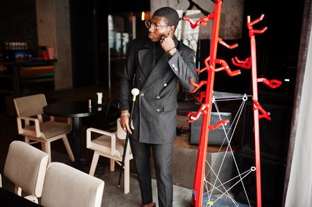Stylish african american gentleman in elegant black jacket and glasses