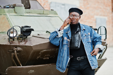 African american man in jeans jacket, beret and eyeglasses, speaking on phone against btr military armored vehicle.