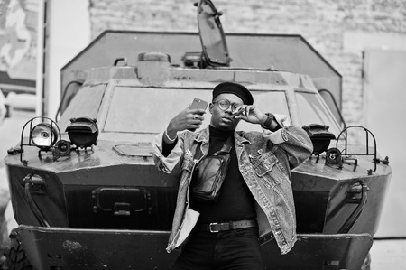 African american man in jeans jacket, beret and eyeglasses, with cigar posed against btr military armored vehicle, and making selfie on mobile phone.