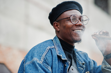 Close up portrait of african american man in jeans jacket, beret and eyeglasses, smoking cigar. Stock fotó