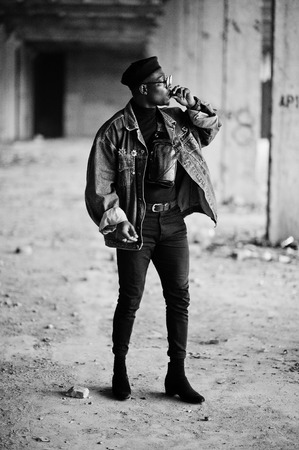 African american man in jeans jacket, beret and eyeglasses, smoking cigar at abandoned factory.