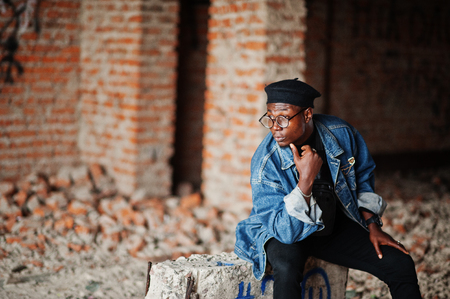 African american man in jeans jacket, beret and eyeglasses at abandoned brick factory. Stock Photo