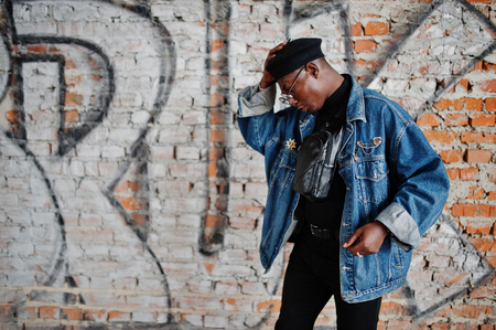 African american man in jeans jacket, beret and eyeglasses against graffiti brick wall with bruk sign.
