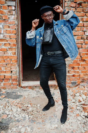 African american man in jeans jacket, beret and eyeglasses against brick wall at abandoned roof. Stock Photo