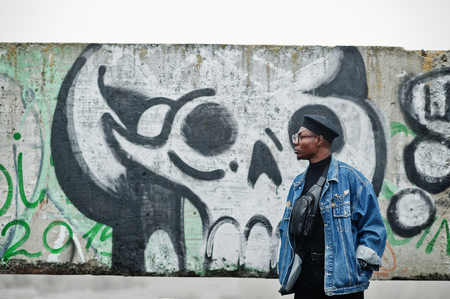 African american man in jeans jacket, beret and eyeglasses against graffiti wall with skull.