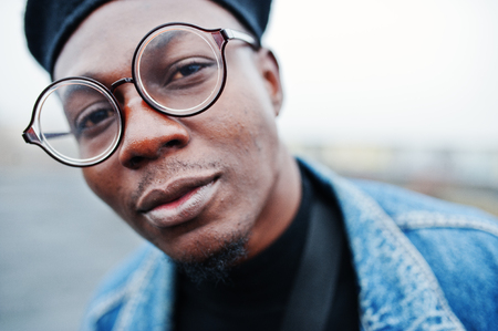 Close up portrait of african american man in jeans jacket, beret and eyeglasses.