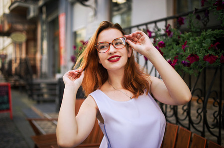 Attractive redhaired woman in eyeglasses posing at street of spring city.