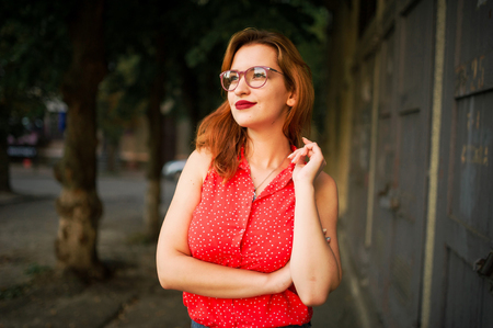 Attractive redhaired woman in eyeglasses, wear on red blouse and jeans skirt posing. Фото со стока