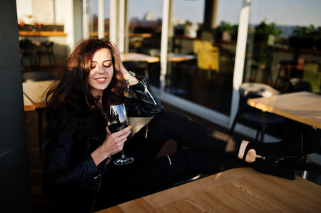 Young curly woman enjoying  her wine in a bar.