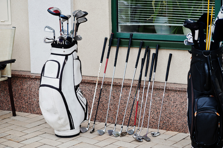Many golf clubs in bag at pavement.