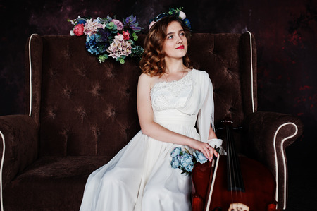 Pretty young gilrl musician in white dress with double bass sitting on brown vintage sofa.