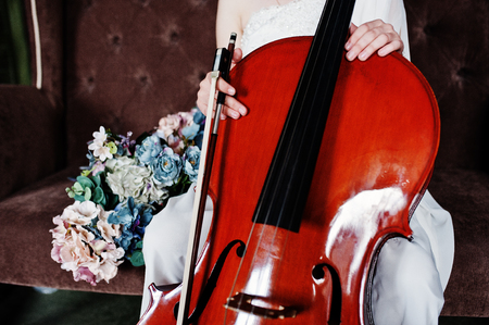 Close up of gilrl musician in white dress with double bass sitting on brown vintage sofa.