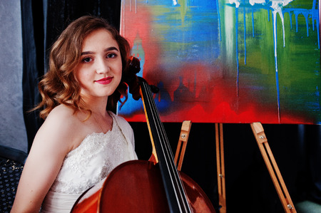 Pretty young gilrl musician in white dress with double bass next to her art painting.