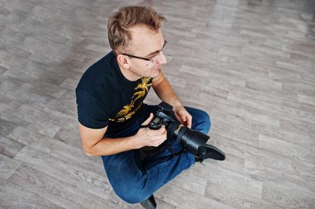 Man photographer sitting on floor at studio. Professional photographer on work. Imagens