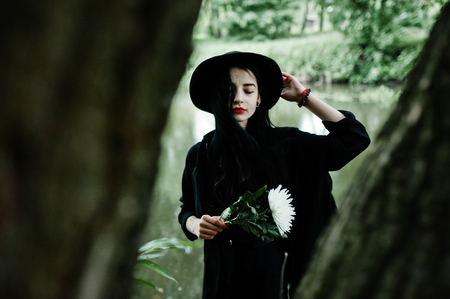 Sensual girl all in black, red lips and hat. Goth dramatic woman hold white chrysanthemum flower at hand against silent lake.