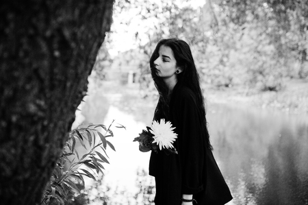 Sensual girl all in black, red lips. Goth dramatic woman hold white chrysanthemum flower at hand against silent lake. Black and white portrait.