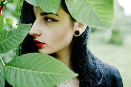 Sensual girl all in black, red lips and earlobe piersing. Goth dramatic woman. Stock Photo