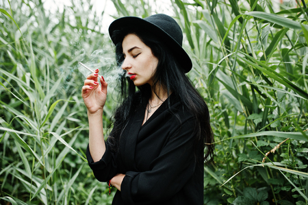 Sensual smoker girl all in black, red lips and hat. Goth dramatic woman smoking on common reed.