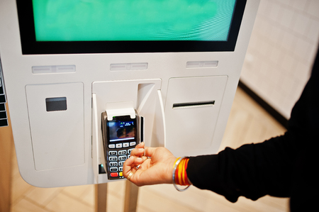 Hands of man customer at store place orders and pay by credit card through self pay floor kiosk for fast food, payment terminal.