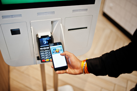 Hands of man customer at store place orders and pay by contactless credit card on mobile phone through self pay floor kiosk for fast food, payment terminal. Pay pass.