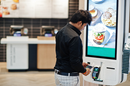 Indian man customer at store place orders and pay by contactless credit card on mobile phone through self pay floor kiosk for fast food, payment terminal. Pay pass.