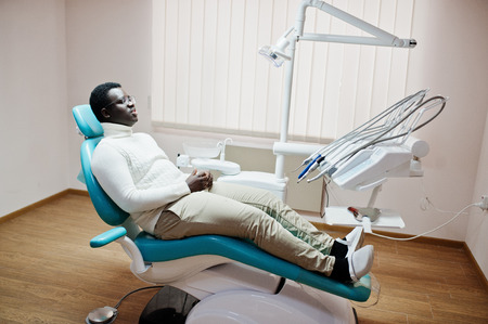 African american man patient in dental chair. Dentist office and doctor practice concept.