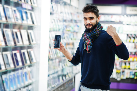 Yes, i found it! Indian beard man customer buyer at mobile phone store choose his new smartphone. South asian peoples and technologies concept. Cellphone shop.