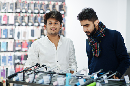 Two indians mans customer buyer at mobile phone store choose a selfie stick. South asian peoples and technologies concept. Cellphone shop.