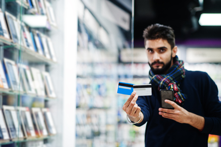 Indian beard man customer buyer at mobile phone store choose his new smartphone and holding credit cards. South asian peoples and technologies concept. Cellphone shop.