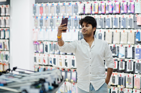 Indian man customer buyer at mobile phone store making selfie on his new smartphone with case. South asian peoples and technologies concept. Cellphone shop.