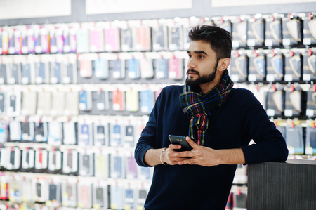 Indian beard man customer buyer at mobile phone store looking on his smartphone. South asian peoples and technologies concept. Cellphone shop. 스톡 콘텐츠