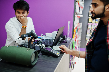 Indian man customer buyer pay for his new smartphone for seller by credit card at mobile phone store. South asian peoples and technologies concept. Cellphone shop.