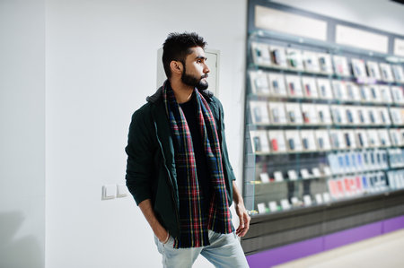 Indian beard man customer buyer in jacket at mobile phone store. South asian peoples and technologies concept. Cellphone shop. Stock Photo