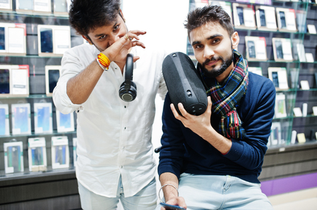 Two indians mans customer buyer at mobile phone store with earphones and wireless speaker listening music. South asian peoples and technologies concept. Cellphone shop. 스톡 콘텐츠