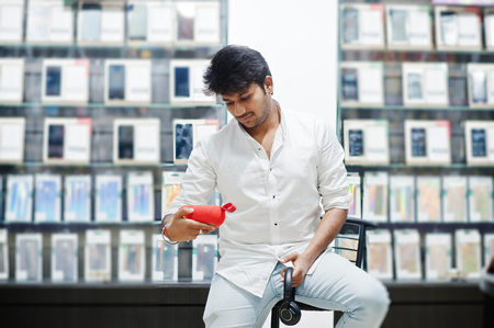 Indian man customer buyer at mobile phone store with wireless earphones and speaker sitting on chair. South asian peoples and technologies concept. Cellphone shop.