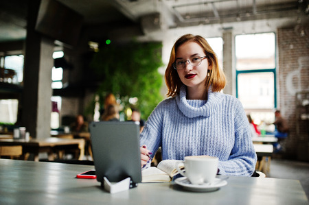 Cheerful young beautiful redhaired woman in glasses using her phone, touchpad and notebook while sitting at her working place on cafe with cup of coffee. 版權商用圖片