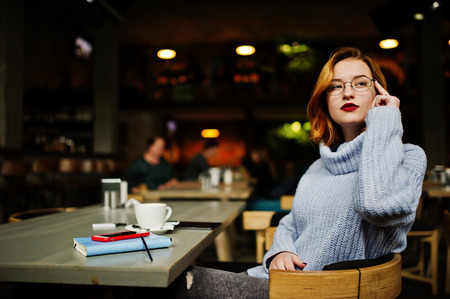 Cheerful young beautiful redhaired woman in glasses sitting at her working place on cafe with cup of coffee.