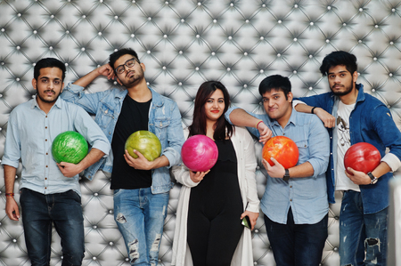 Group of five south asian peoples having rest and fun at bowling club, posing against silver wall with balls at hands.