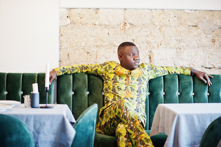 Friendly afro man in traditional yellow clothes resting on the couch at restaurant. Chill out after work day.