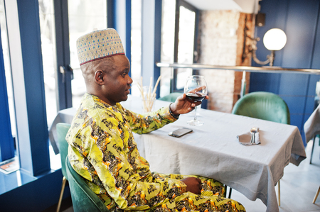Friendly afro man in traditional yellow clothes and cap drinking red wine at restaurant.