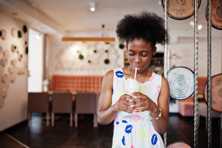 Ð¡heerful african american young woman in summer dress at cafe drinking milkshake.