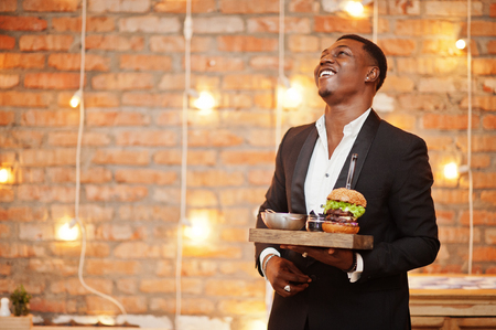 Respectable satisfied young african american man in black suit hold tray with double burger against brick wall of restaurant with lights.