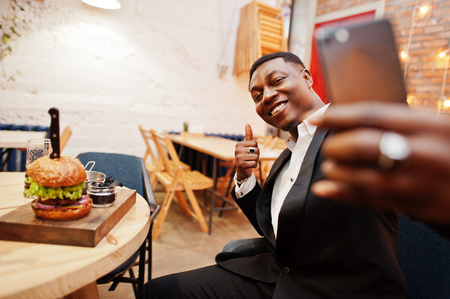 Respectable young african american man in black suit sitting in restaurant and making selfie against tasty double burger and show thumb up. 写真素材